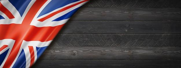 黒い木の壁にイギリス、イギリスの旗。水平方向のパノラマバナー。