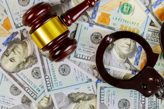 United states dollars bills cash on wooden judge gavel and handcuffs, justice desk