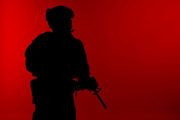 Специальные операции корпуса морской пехоты сша командуют рейдером marsoc с оружием. силуэт морского специального оператора красном фоне