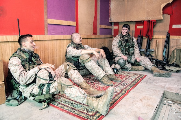 United states marines in camouflage uniform and ammunition sitting on floor at combat outpost or temporary base on mission, talking in relaxing atmosphere, resting after hard day on military service