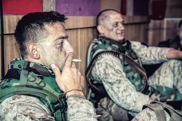 위장 제복을 입은 미 해병대와 탄약이 전투 전초 기지 또는 임무 임시 기지 바닥에 앉아 편안한 분위기에서 이야기하고 병역에서 힘든 하루를 보낸 후 휴식
