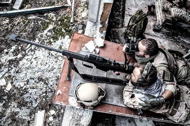United states navy seal sniper team firing with large caliber, anti material sniper rifle with optical sight from ruined, abandoned building. elite members of anti-terrorist squad in modern warfare