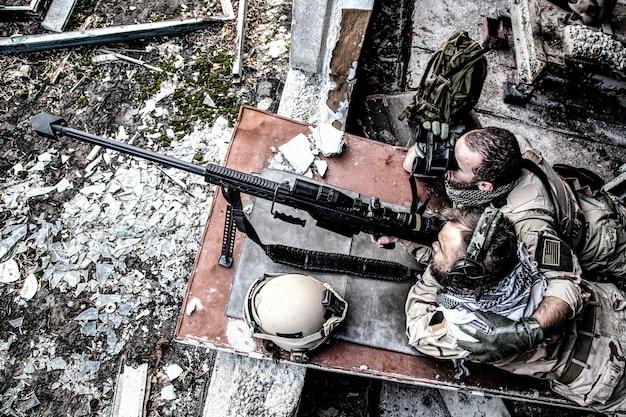 미국 해군 seal 저격 팀이 파괴되고 버려진 건물에서 광학 시력을 갖춘 대구경, 대물 저격 소총으로 발사합니다. 현대 전쟁에서 대테러 부대의 엘리트 구성원
