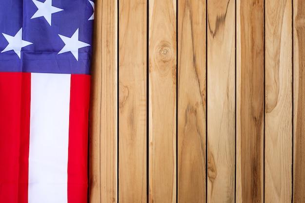 木製のテーブルの背景にアメリカ合衆国の旗。退役軍人、記念碑、独立記念日(7月4日)と労働者の日の概念の米国の休日