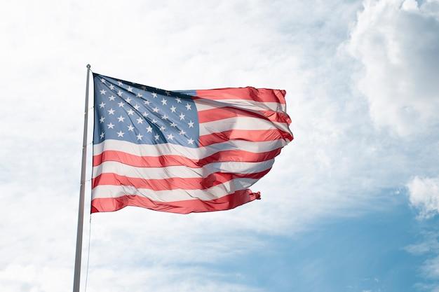 Флаг соединенных штатов америки развевается над облачным и голубым небом