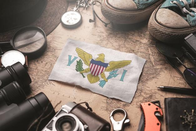 古いビンテージマップ上の旅行者のアクセサリーの間に米国領ヴァージン諸島の旗。観光地のコンセプト。