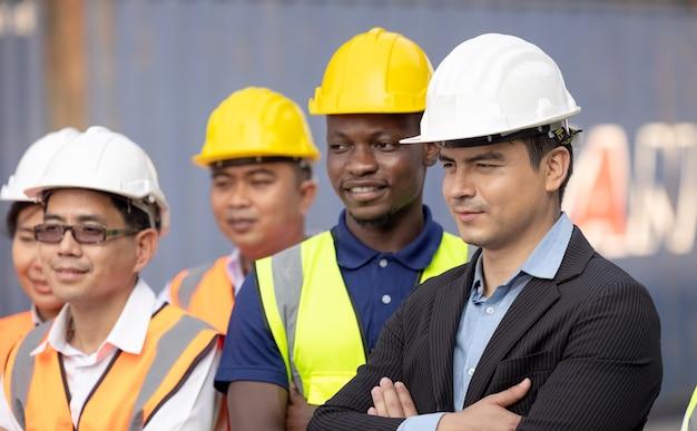 団結と成功のコンセプト。コンテナヤードで手をつないで立っているエンジニアチームの人々の底面図。