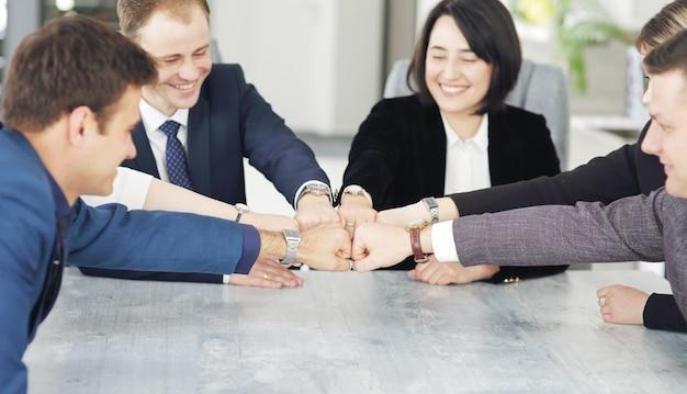 Концепция единства и совместной работы молодых деловых людей, складывая руки вместе.