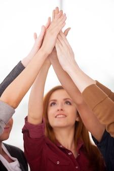 Единство людей. группа веселых молодых людей, стоящих рядом и держащихся за руки