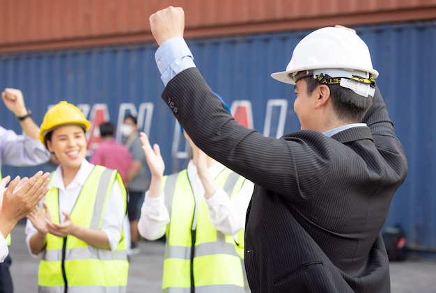 Unity and success concept.bottom view of engineer team people standing hands holding together at the container yard.