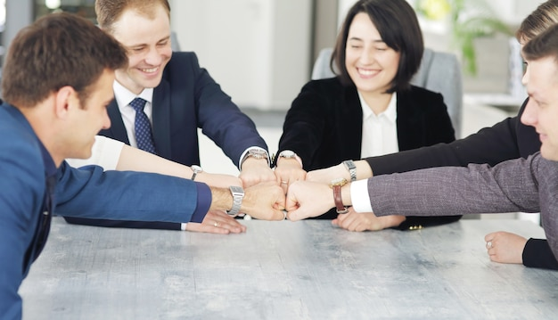 Unity and teamwork concept of young business people folding their hands together.