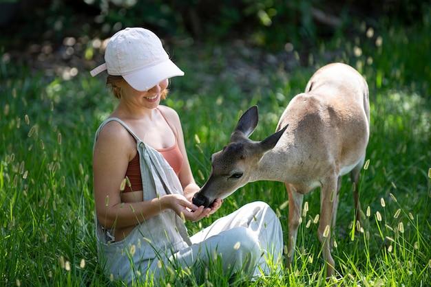 자연 소녀와의 화합은 공원에서 새끼 사슴 동물에게 먹이를 주는 밤비 사슴 야생 동물 개념 여자를 먹입니다.