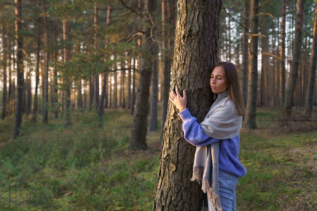 自然との一体感秋の森を歩いて目を閉じて松の木の幹を抱き締める穏やかな少女