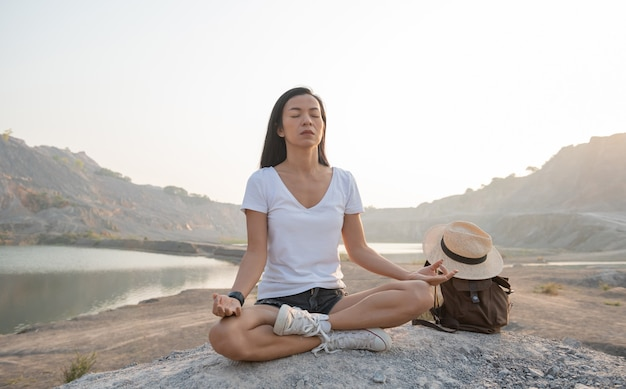 自然との一体感。湖の近くで屋外で瞑想をしている若い女性