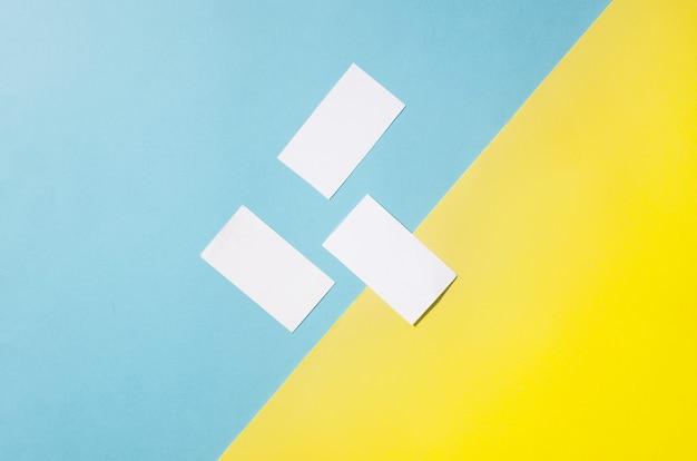 파란색과 노란색 종이 배경에 그림자와 함께 3 개의 명함 이랑 템플릿의 보편적 인 빈 템플릿. 디자인을 배치하십시오.