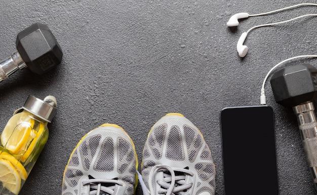 コピースペースを持つ黒いアスファルト背景に普遍的な女性と男性のフィットネス機器:ダンベル、ヘッドフォン付き電話、灰色のスニーカー。