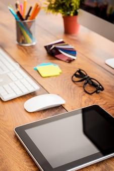 Универсальный помощник в работе. крупный план удобного рабочего места в офисе с деревянным столом и цифровым планшетом, лежащим на нем