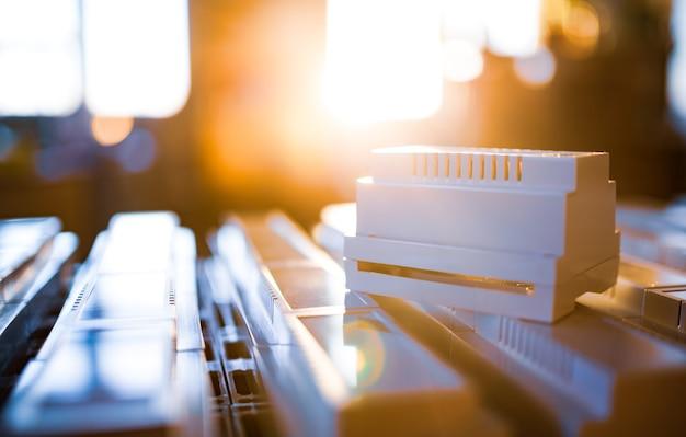 직렬 무선 전자 제품 제조를 위한 범용 플라스틱 케이스는 창에서 나오는 황금빛 백라이트 저녁 빛입니다. din 레일에 장착하기 위한 플라스틱 케이스.