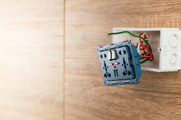 Universal wall outlet ac power plug with usb port in a plastic box on a wooden wall.