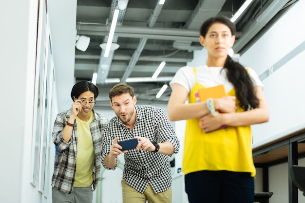 University bullying. nervous ashamed girl walking in the university and suffering from two men taking photos of her and laughing