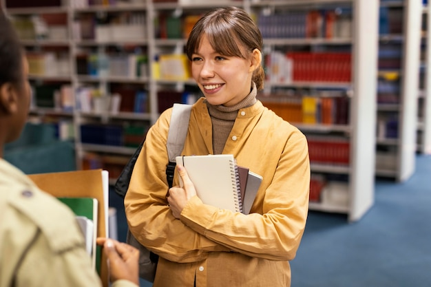 Коллеги по университету разговаривают в библиотеке