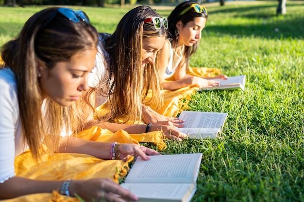 Студентки университета лежат на траве в парке утром и читают книгу в мягкой обложке