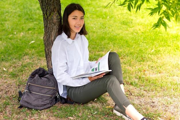 本や草の上に座って教科書を読む大学の女の子