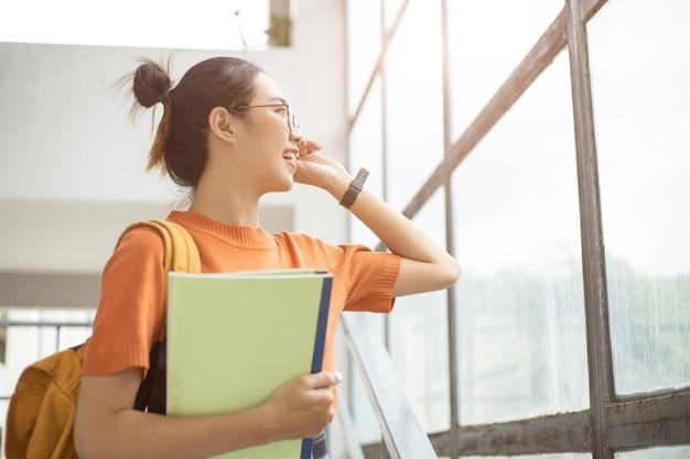 大学の女の子スマートティーン探し窓幸せな笑顔とメガネオタクアジアの女性