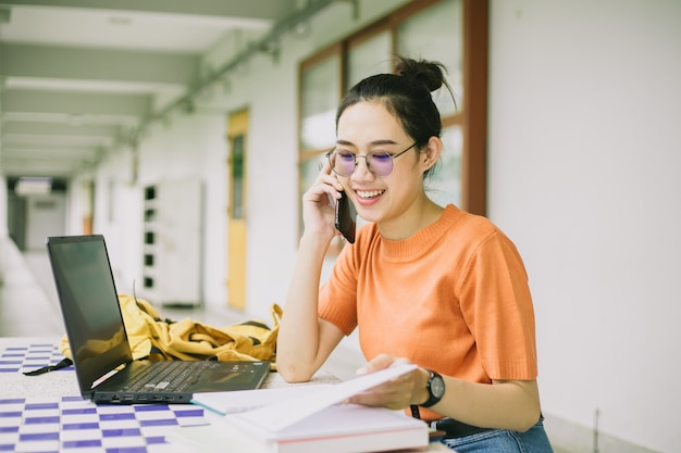 University girl teen using phone call talking with friend while working in campus
