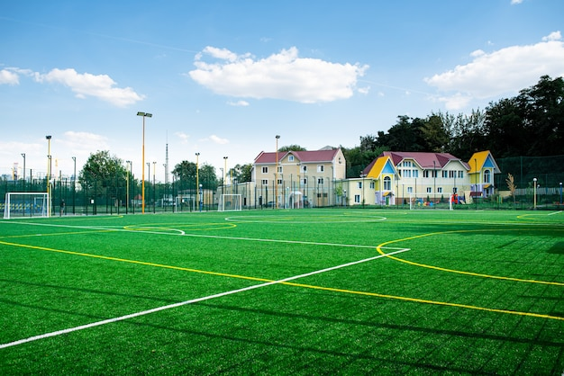大学または学校のサッカー場のスタジアム、緑の芝生の背景。