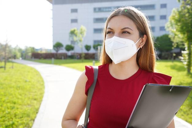 Ffp2kn95フェイスマスクを持つ大学生の女の子が屋外で横を向いているフォルダを保持しています