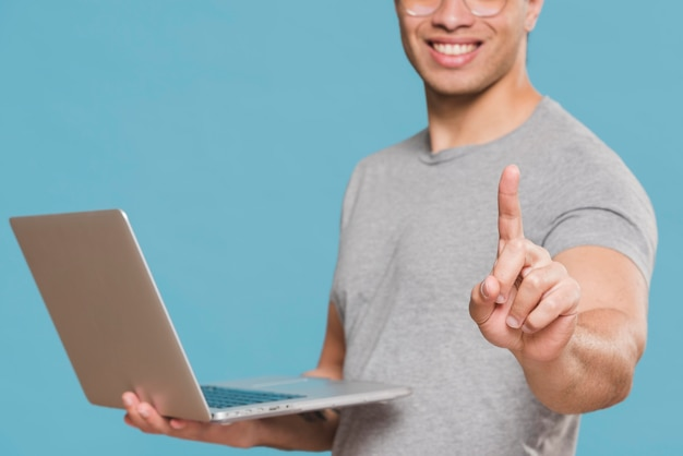 University student holding his laptop and msiles