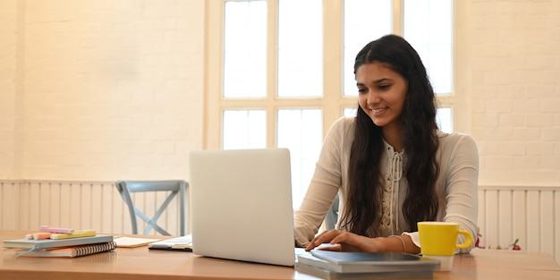 A university student is learning lessons online while sitting at the wooden working desk.