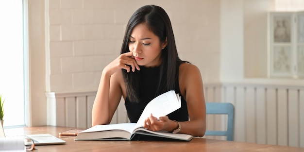 A university student is reading a book while sitting at the wooden working desk.