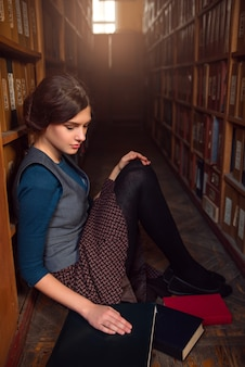 図書館の床に座っている大学生。