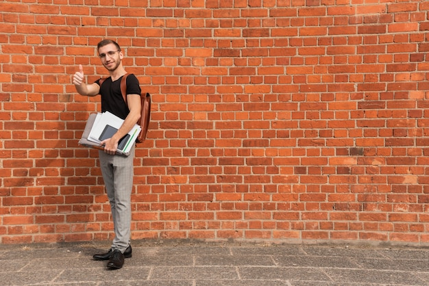 University student standing in front of a brick wall copy space background