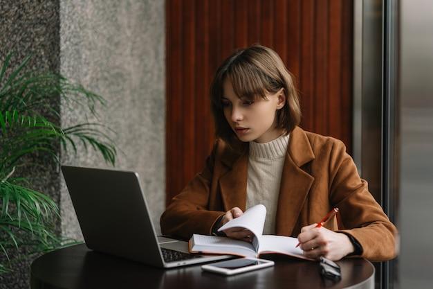 University student using laptop computer, studying, reading, learning language, exam preparation