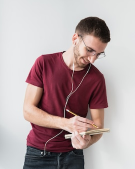 University student wearing headphones and writing