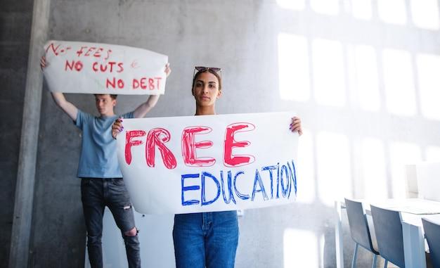 대학생 활동가들이 실내에서 시위하고 무료 교육 개념을 위해 싸웁니다.