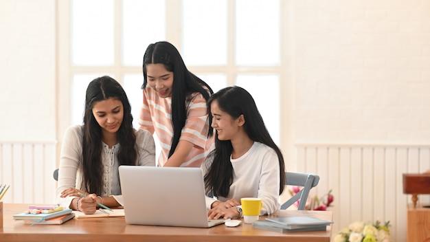 Студенты университета занимаются электронным обучением, сидя вместе в гостиной.