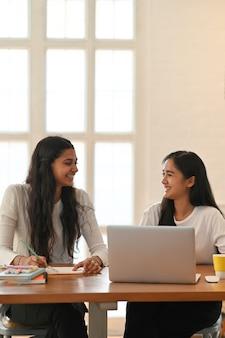 Студенты университета сидят вместе перед ноутбуком за рабочим столом.