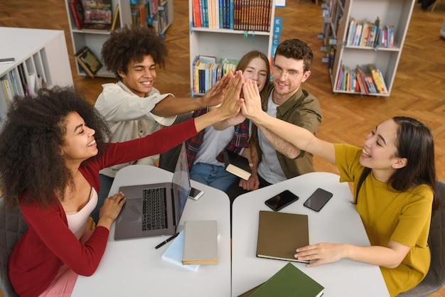 大学生は一緒に図書館で勉強しています。チームワークと準備の概念