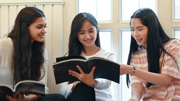 大学生がリビングルームで一緒に座っている間、話したり雑誌を読んだりしています。