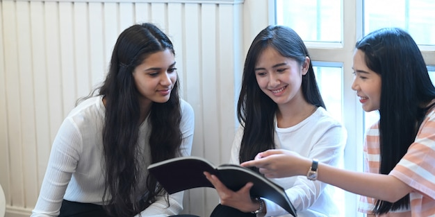University students are talking and reading a magazine while sitting together in the living room.