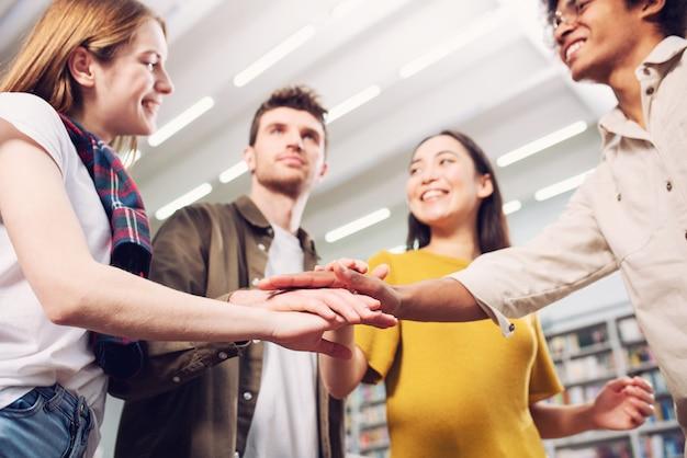 大学生は手を合わせます。チームワークとパートナーシップの概念