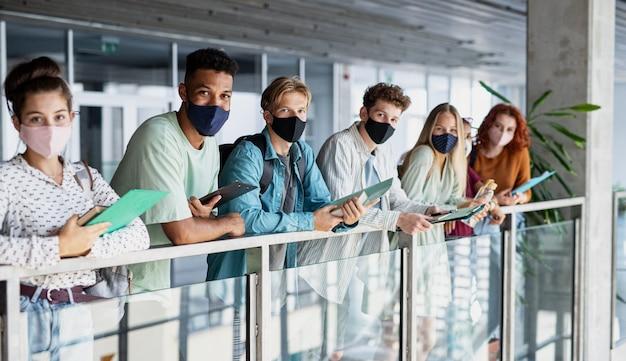 Студенты университета стоят и смотрят в камеру в помещении с коронавирусом и возвращаются к нормальной концепции