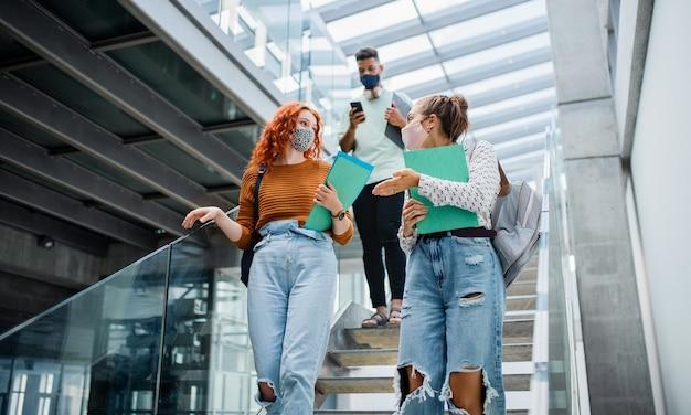 Студенты университета спускаются и разговаривают по лестнице в помещении, концепция коронавируса.