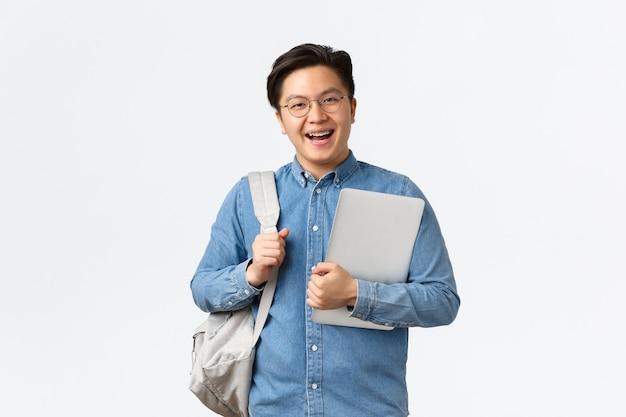 大学、留学、ライフスタイルのコンセプト。バックパックとラップトップで立っているメガネで陽気なアジア人の笑顔。白い背景の上にポーズをとって、クラスに行く途中の学生
