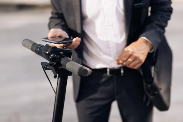 Неизвестный бизнесмен в классическом костюме подходит к электросамокату и использует приложение для мобильного телефона