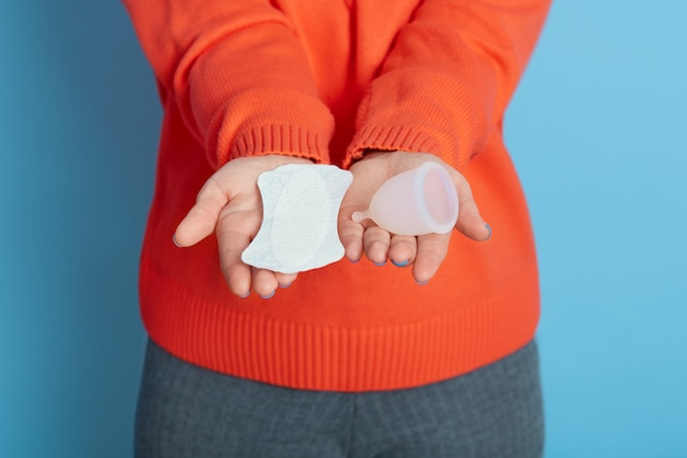 両手に衛生パッドと月経カップを持っている未知の女性